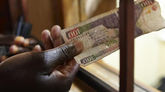 Person pays cash at health facility reception, Kenya